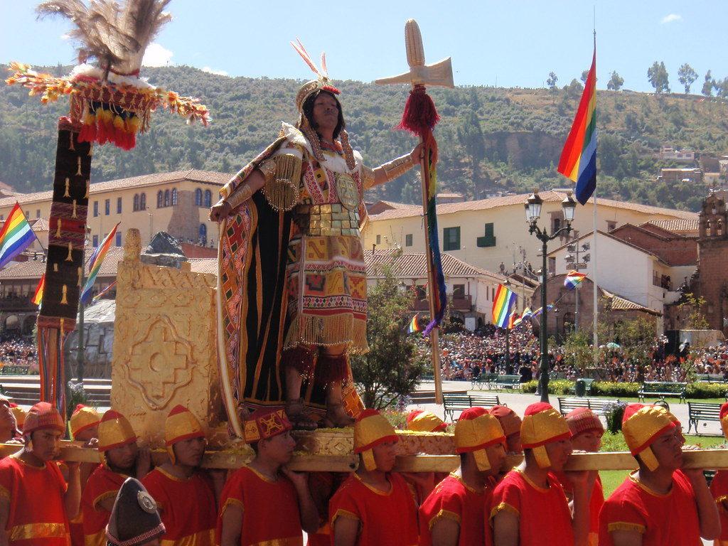 On peut voir le Grand Inca debout une chaise à porteurs. Il est porté par des hommes en costumes rouges avec un chapeau couleur rouge/or. Le Grand Inca aborde une pose fière et tient dans sa main une sorte de lance. Guide de l'Inti Raymi.