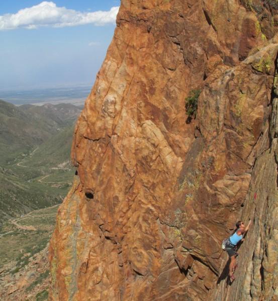 Une grimpeuse escalade la falaise de Los Arenales, au loin le paysage magnifique