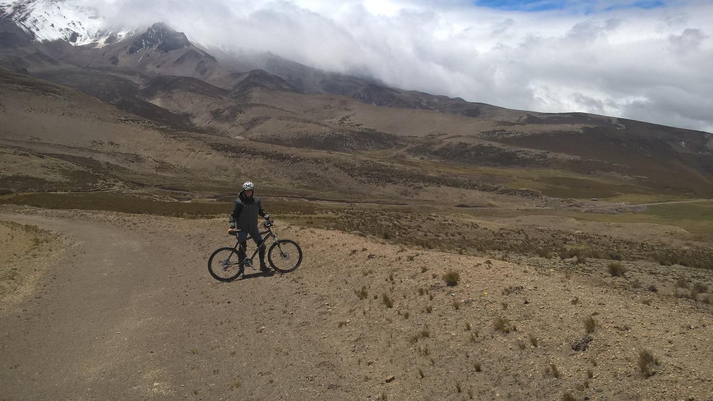 Corentin à côté de son vélo devant le volcan