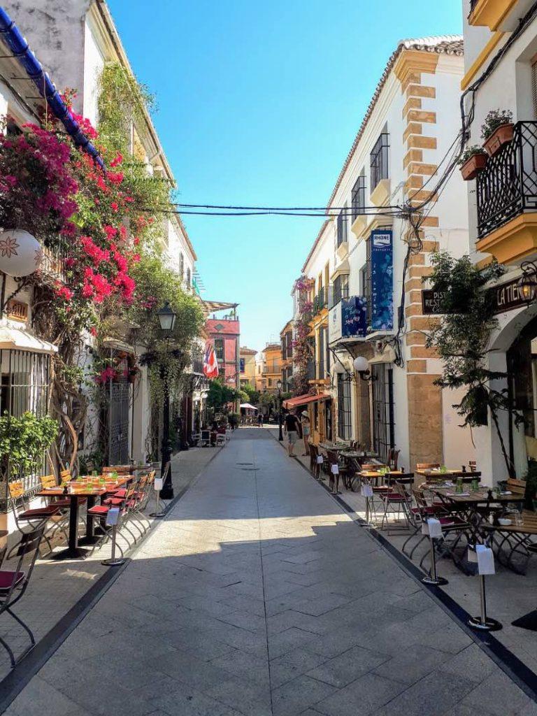 Visiter l'Andalousie : une rue passante de Marbella encadrée par des restaurants et des bars